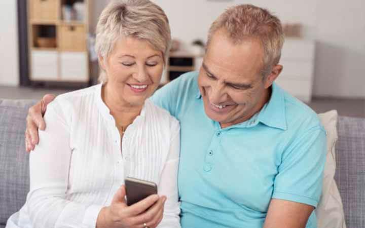 casal feliz com o celular na mão vendo sobre empréstimo consignado