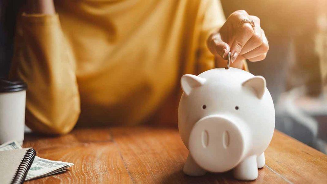 mulher guardando dinheiro num porco mostrando como juntar dinheiro ganhando pouco