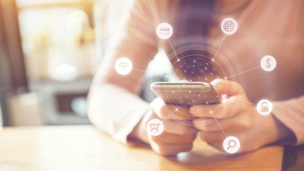mão com celular e vários ícones saindo da tela mostrando como ganhar dinheiro com infoprodutos