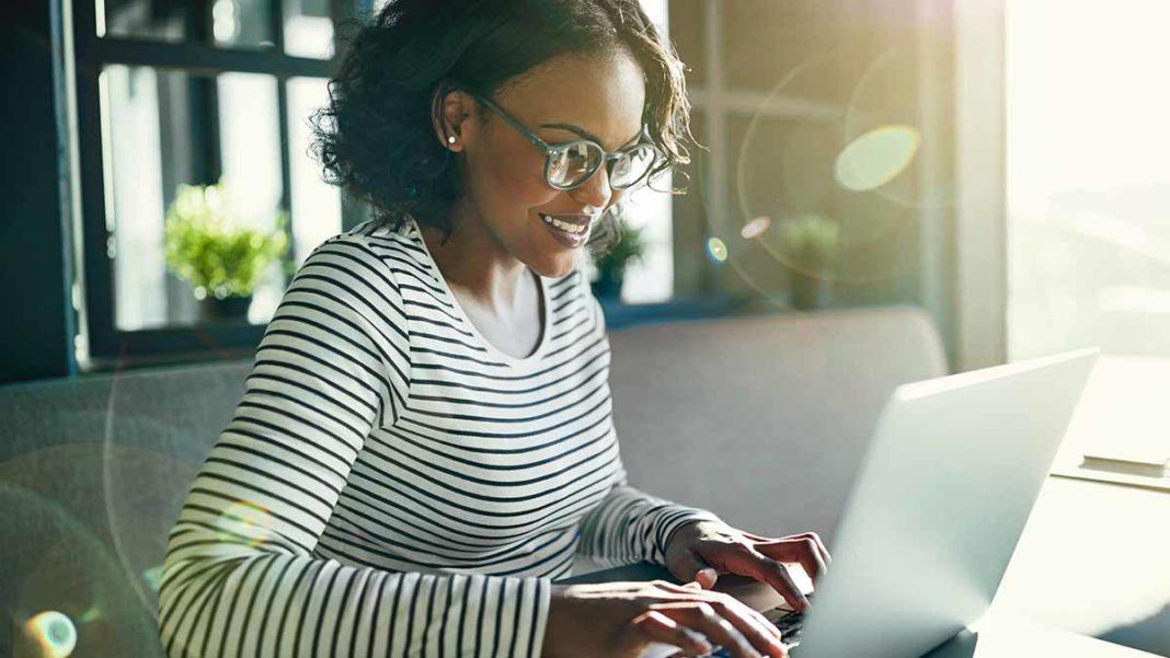 mulher feliz no computador contratando empréstimo pessoal online