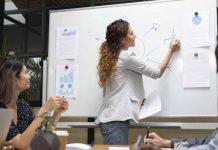 mulher mostrando no quadro branco como avançar em sua carreira profissional