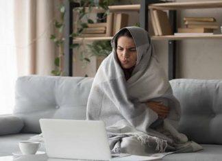 Mulher toda coberta, incluindo a cabeça, sentada no sofá a frente do computador em uma sala, ao fundo uma estante com decorações e plantas