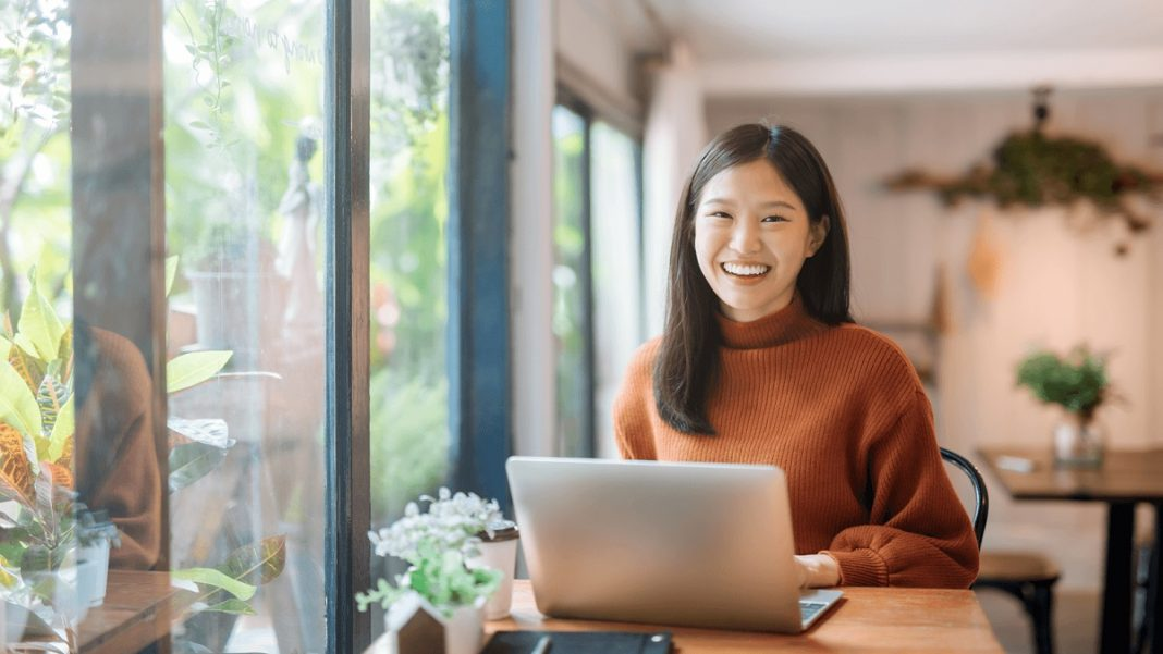 Empréstimo pessoal online em financeiras, mulher asiática com computador em uma sala cheio de vidros e arvores, com um semblante de felicidade