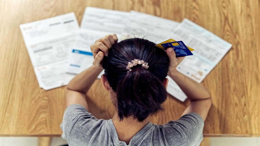Empréstimo pessoal para negativado: o que é, como funciona e opções, foto com visão aerea de uma mulher com as mão na cabeça, sobre alguns papeis de contas e boletos