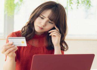 Mulher segurando um cartão de crédito na frente do computador com um semblante de duvida como se quisesse entender como funciona o cartão do empréstimo consignado