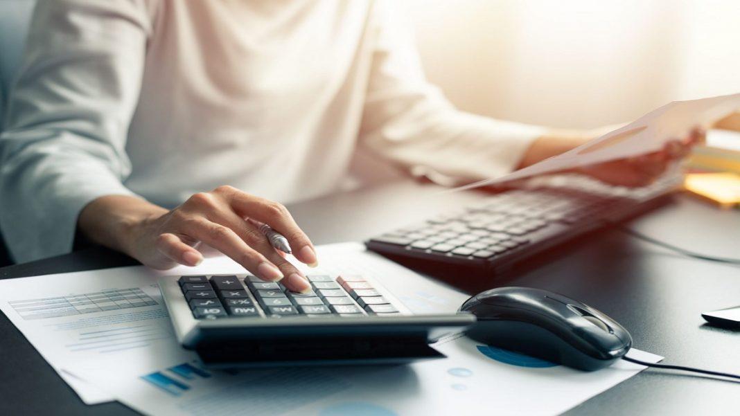 Entenda como funciona o empréstimo pessoal online com garantia, pessoa usando calculadora e computador dando a impressão que está simulando um empréstimo pessoal online