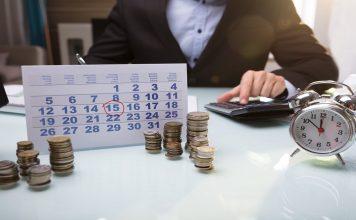Entenda tudo sobre os prazos do empréstimo consignado,Uma pessoa de terno, na mesa com um calendário e 8 montes de moedas senda quatro do lado esquerdo e quatro do lado direito e no canto direito temos um despertador cromado