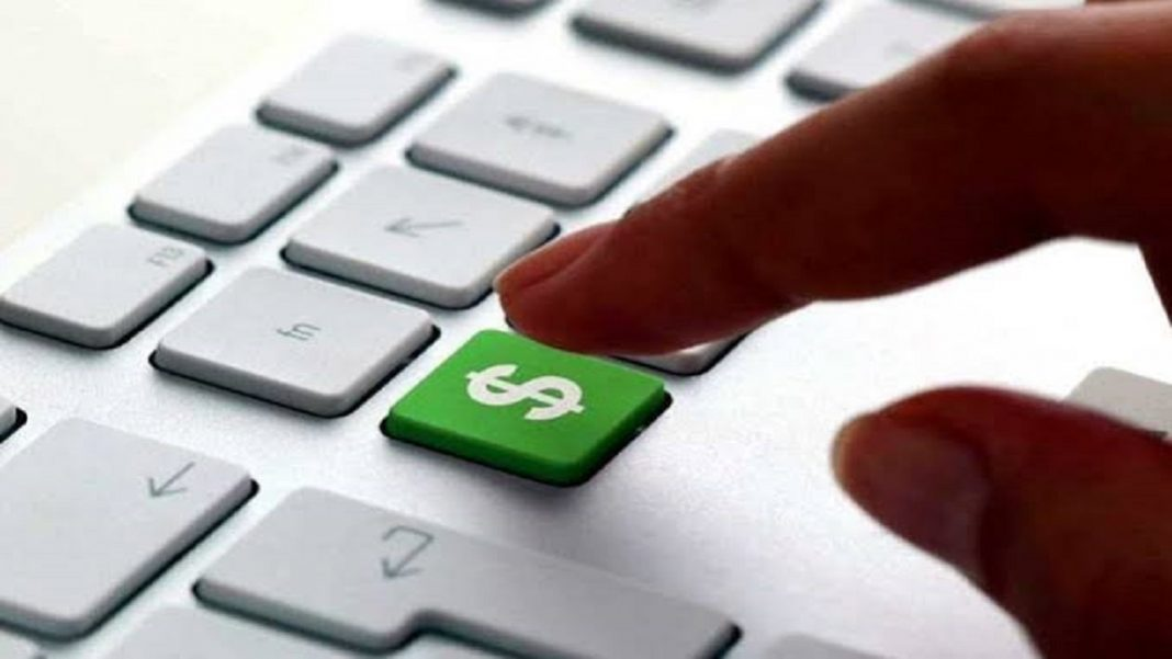 Precisando de Grana saiba como ganhar dinheiro na internet, teclado de um computador com um botao verde com um simbolo de cifrão quase apertado por um dedo.