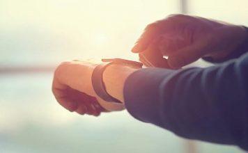 Smartwatch. como escolher o ideal, um braço de uma pessoa com o Smartwatch e um dedo como se fosse usar essa tecnologia, em um ambiente levemente desfocado pela foto.