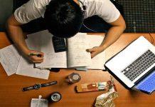 Uma foto vista por cima, no qual tem um homem estudando em uma mesa, a sua frente tem objetos para o estudo e ao lado um notebook. Estaudando para concursos públicos