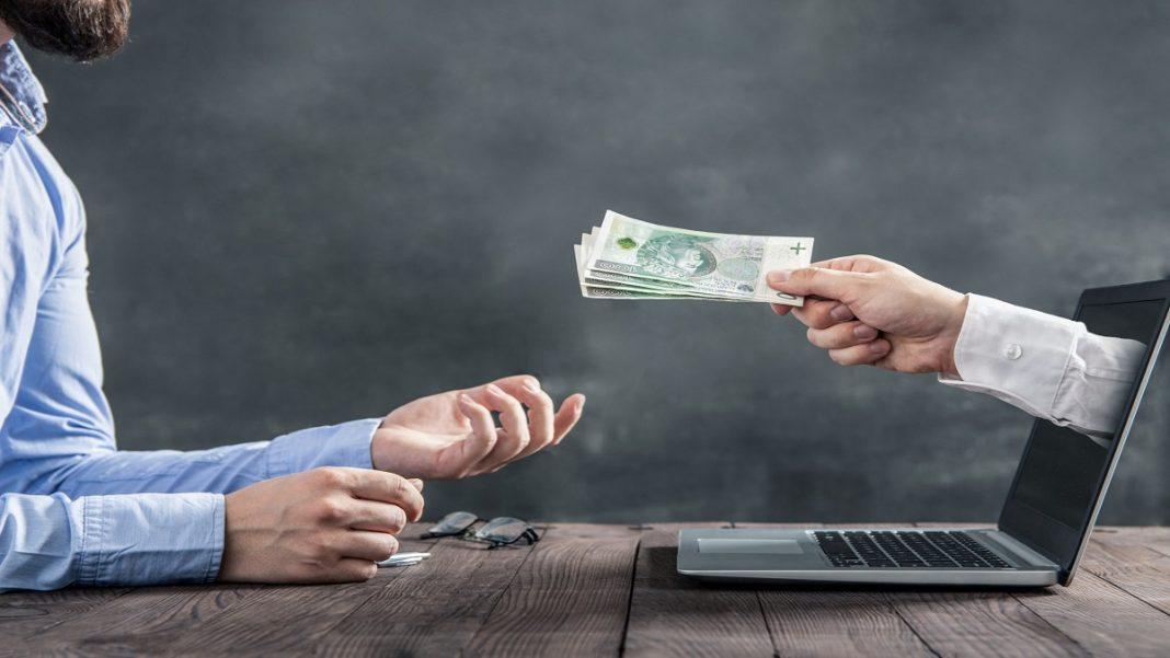 Empréstimo pessoal online, aprenda a aumentar a renda no final de ano, uma pessoa recebendo dinheiro de uma mão que está saindo da tela do notebook, estão em uma sala com parede levemente acinzentada e o note book sobre uma mesa de madeira.