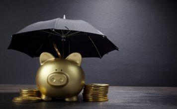 Empréstimo pessoal online X Empréstimo com agiota, Cofrinho de porco dourado com guarda chuvas e moedas ao seu redor