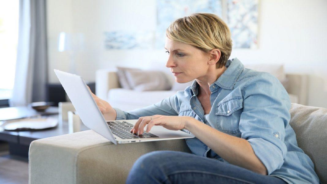 Mulher de camisa e calça jeans azul, sentada no sofá com o notebook olhando para a tela para ver as opções de empréstimo pessoal online em bancos.