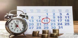 uma mesa com despertador moedas e um calendário com o dia quinze circulado, sugerindo que quase metade dos brasileiros buscaram sobre empréstimo em agosto.
